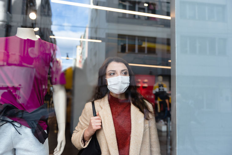 Woman wearing mask standing by clothing store