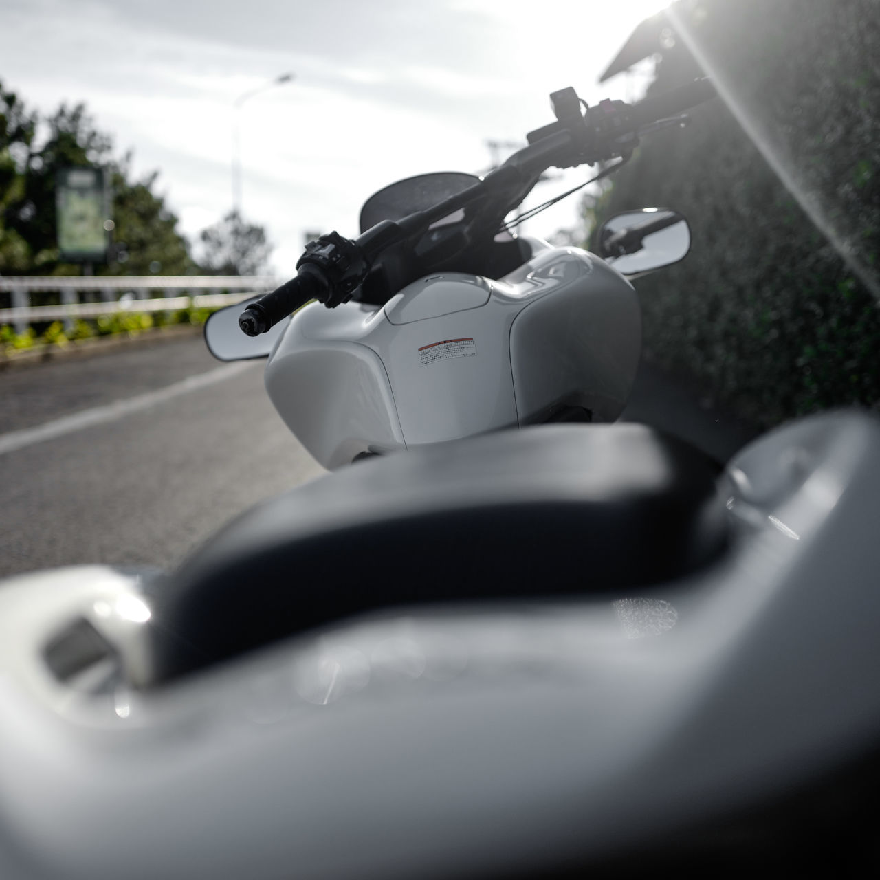 transportation, land vehicle, mode of transport, motorcycle, road, selective focus, day, side-view mirror, steering wheel, car, no people, close-up, helmet, scooter, outdoors, speedometer, sky