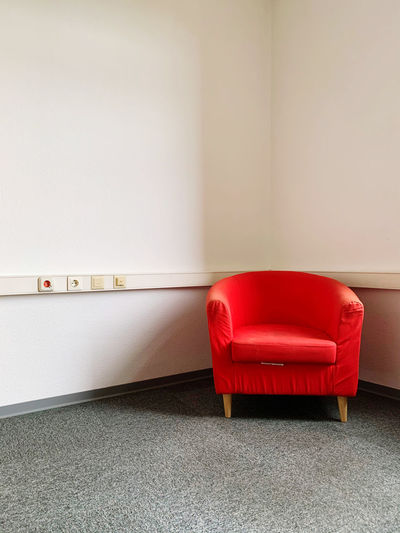Empty chair against red wall