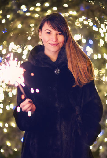 Portrait of smiling woman standing at illuminated christmas tree
