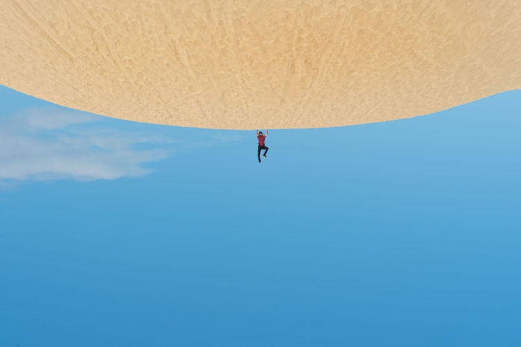 Upside down image of man doing handstand at desert