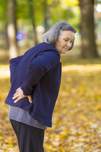 Woman With Backache Standing At Public Park