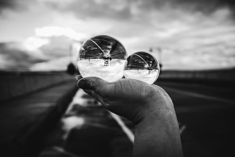 Close-up of person holding glass against sky