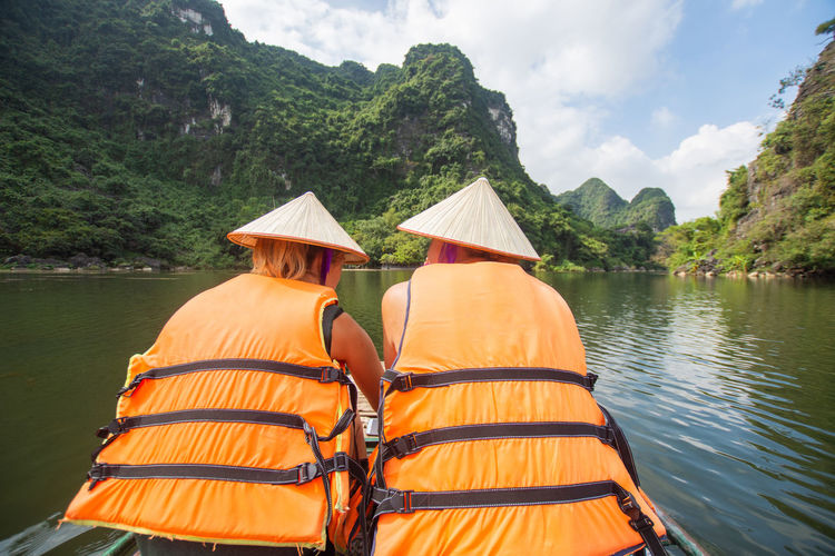 tourist sitting on boat at Trang An, Ninh Binh, Vietnam. Water Tree Lake Nature Rear View Plant Beauty In Nature Mountain Day Sky Hat Real People Cloud - Sky Clothing Nautical Vessel Scenics - Nature Transportation Non-urban Scene Outdoors