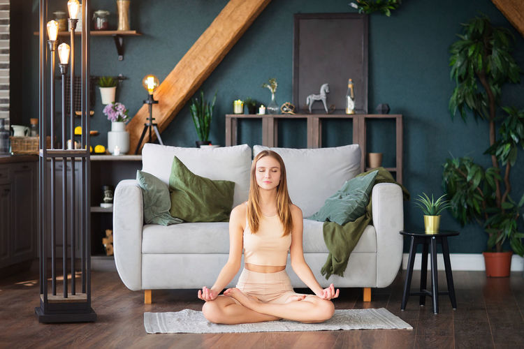 Full length of young woman meditating at home
