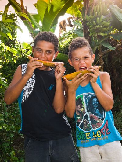 Children Eating Paw Paw Fruit Pacific Bonding Casual Clothing Cherry Blossoms Children Eating Day Food On The Go Front View Fruit Green Color Looking At Camera Pacific Ocean Paw Paw Fruit Paw Paw Fruit Person Togetherness Traveling Tropical Vivid International
