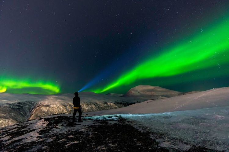 Man Standing On Mountain Against Aurora Polaris