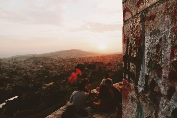People looking at city buildings against sky