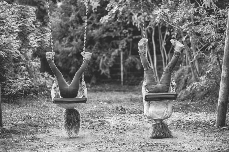 Rear view of girls with upside down hanging on swings in park