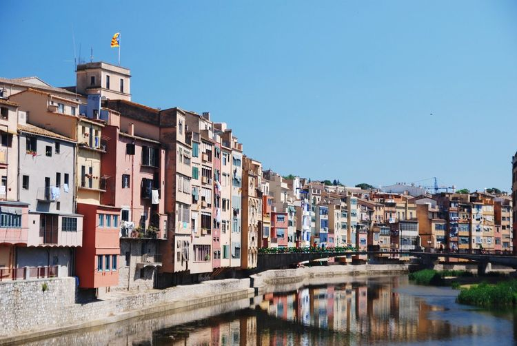 Residential buildings by canal against clear sky