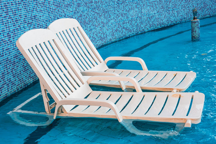 High angle view of empty chairs at swimming pool