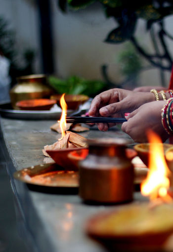 Cropped Hands Of Woman Igniting Incense