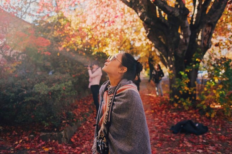 Side view of young woman standing against tree during autumn