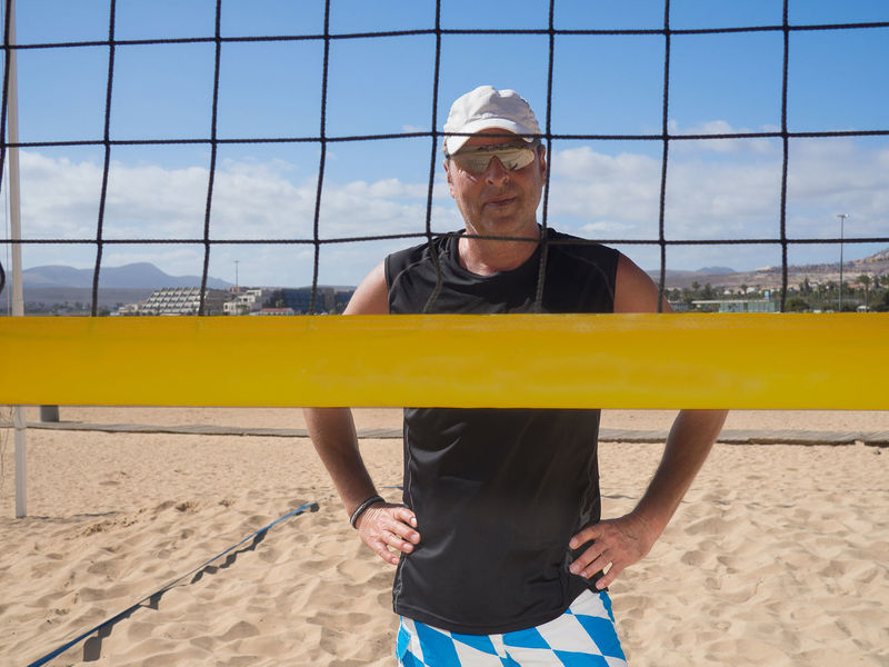 Portrait of a handsome athletic man with sunglasses smiling behind the beach volleyball net Adult Ambitious Athlete Ball Beach Beach Volleyball Do Sports Dredge Fit Fitness Game Holiday Looking At Camera Man Middle Ages Motion Outdoors Play Recreational Pursuit Sand Smiling Sport Sportive Training Volleyball