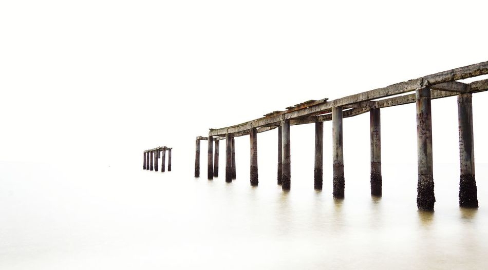 Low angle view of wooden posts against clear sky