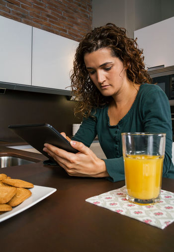 Young woman having breakfast in the kitchen and looking at the tablet Vertical Female Girl Orange Juice  Technology Comfortable Cozy Unmarried Enjoying Relax Sitting One News Modern Serious Portrait Biscuits Indoor Internet Real Adult Curly Hair Young Concentrated Journal Sunday People Digital Holding Reading Web Napkin Shopping Lifestyle Caucasian Home Kitchen Tranquility Morning Interested Tablet Using Looking Breakfast Pajama Woman Single