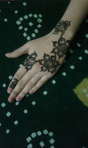 Cropped Image Of Woman Hand Showing Henna Tattoo On Fabric