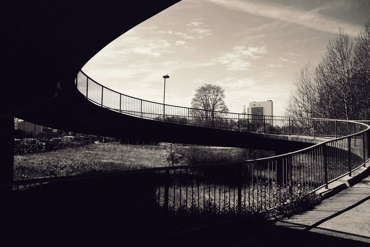 Bridge over canal in city against sky