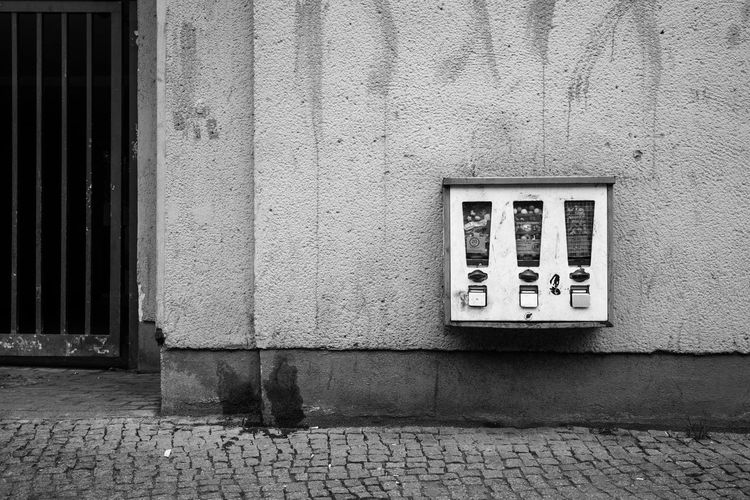 Gumball machine mounted on building wall by street