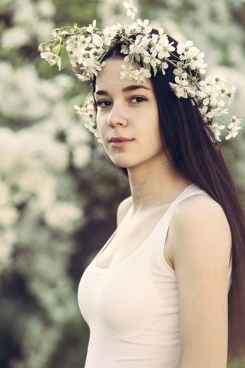 Portrait Of Young Woman Wearing Flowers While Standing At Park