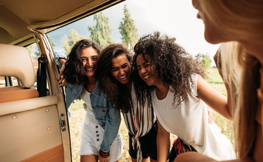 Happy female friends near van