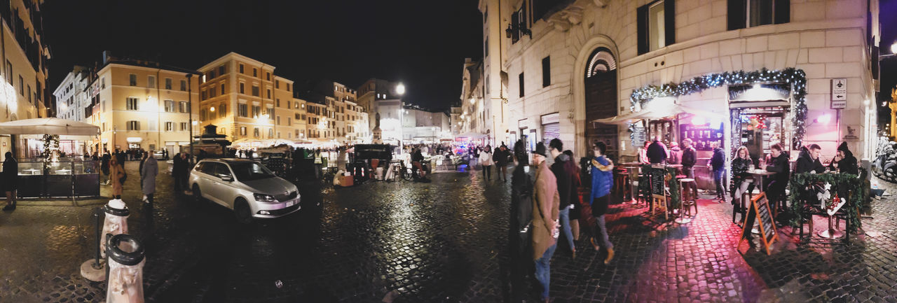 People on street by illuminated buildings in city at night
