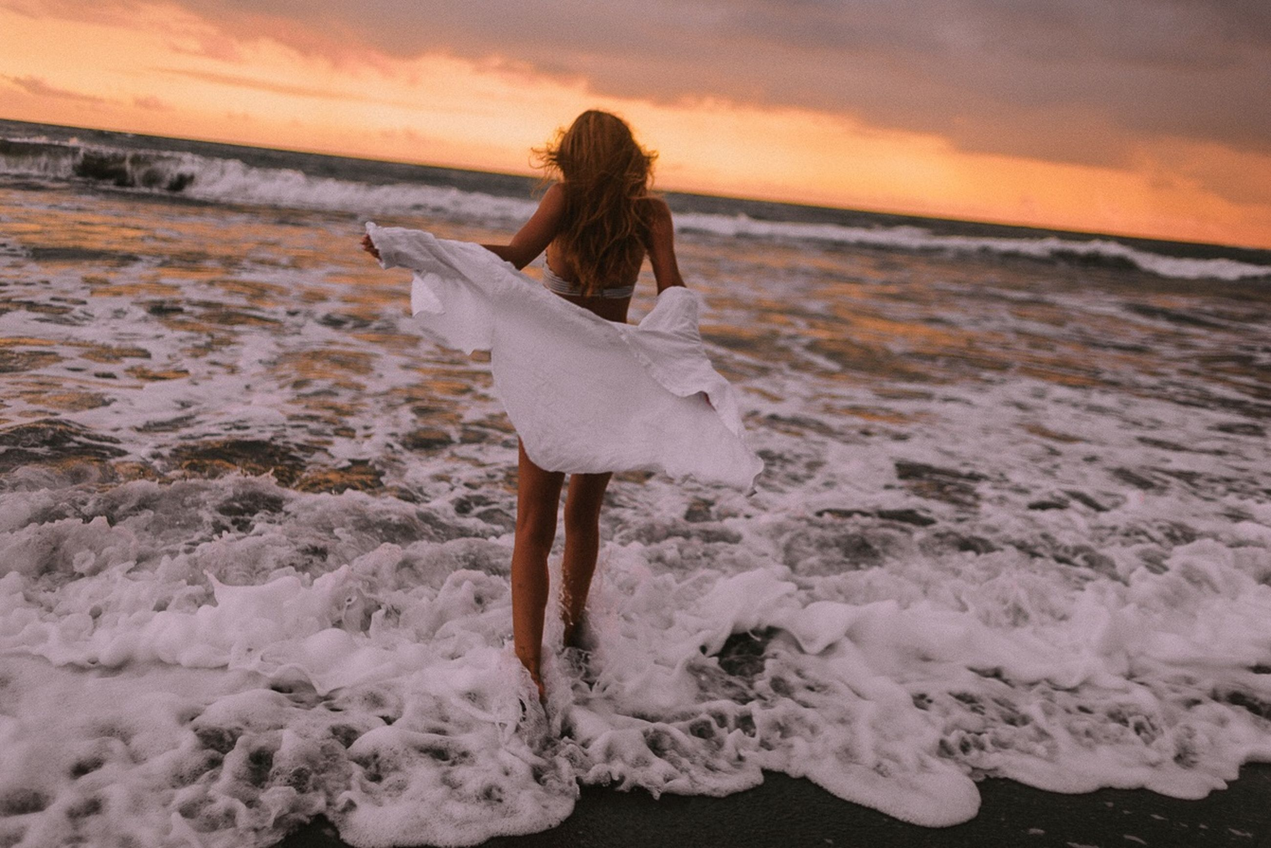 sea, sunset, water, beach, land, sky, leisure activity, motion, horizon, horizon over water, one person, beauty in nature, women, lifestyles, wave, real people, surfing, scenics - nature, aquatic sport, hairstyle, hair, outdoors