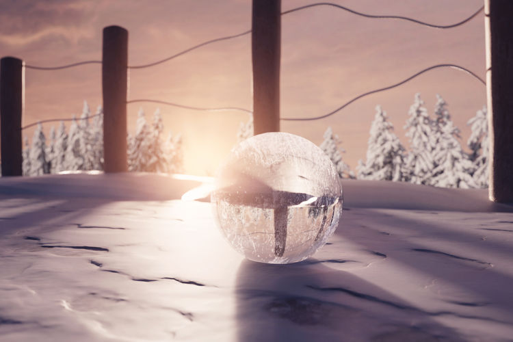 crystal ball on snow with foot steps in the evening sunshine Crystal Ball Glass Ball Frozen Evening Sunset Winter Snow Cold Temperature Nature Warm Ice Covering Fence Wooden Post Sunlight Close-up Ice Reflection Beauty In Nature Focus On Foreground Foot Steps Shadows Countryside Nature