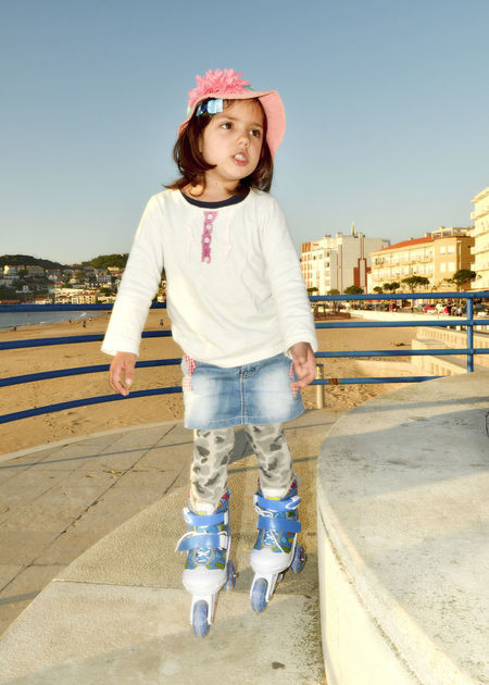 4 years girl playing with rollerblades Architecture Casual Clothing Childhood Clear Sky Day Elementary Age Front View Full Length Girls Happiness Leisure Activity Looking At Camera One Person Outdoors People Portrait Railing Real People Sky Smiling Standing