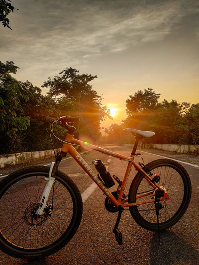 Bicycle by road against sky during sunset