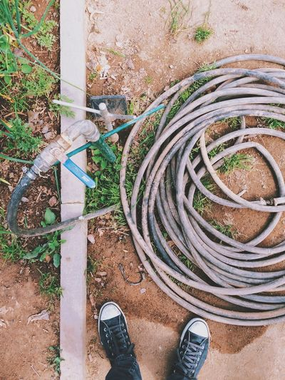 Low section of man standing by garden hose
