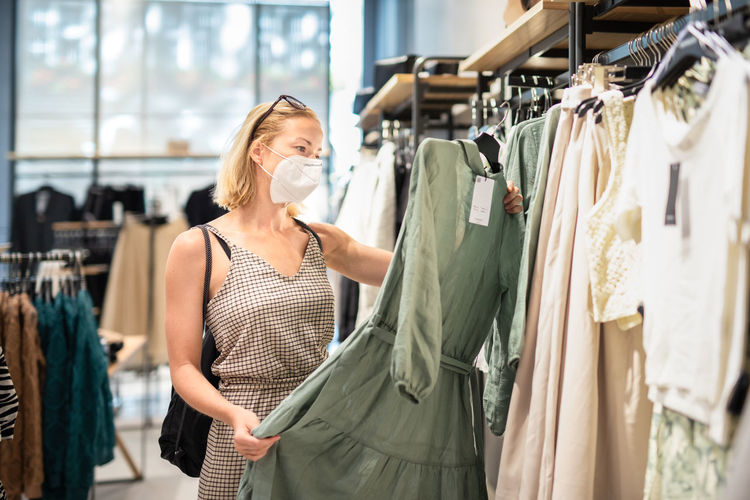 Mid adult woman wearing mask standing in clothing store