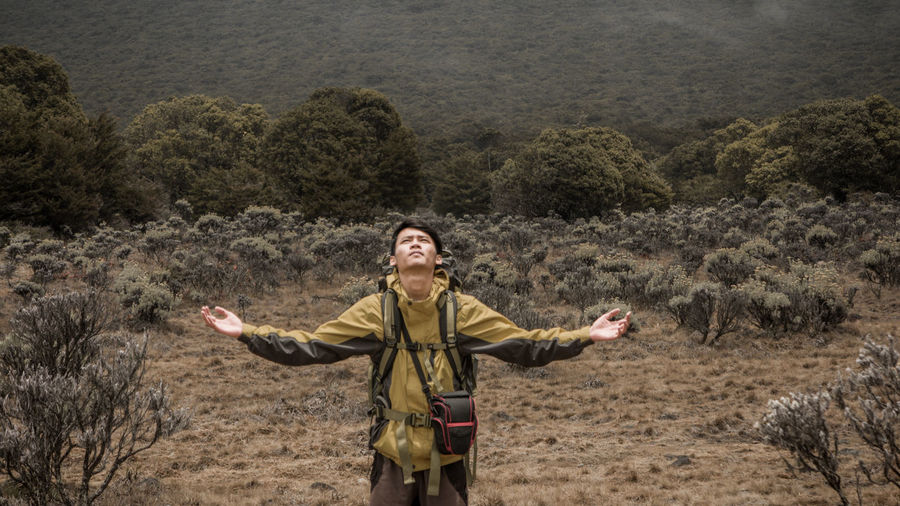 Full length of man with arms outstretched standing on land