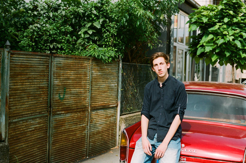 Analogue Photography Adult Architecture Building Exterior Casual Clothing Contemplation Day Filmisnotdead Front View Leisure Activity Looking At Camera Mode Of Transportation One Person Outdoors Plant Portrait Red Car Standing Three Quarter Length Transportation Tree Young Adult Young Men