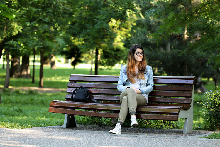 Thoughtful woman sitting on bench at park