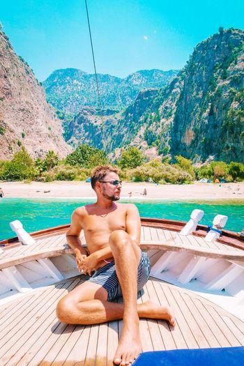 Shirtless man sitting in boat on sea