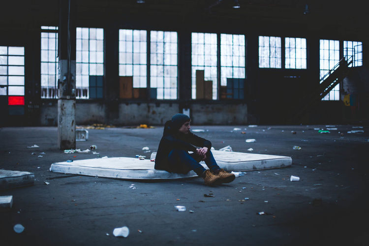 Man sitting on mattress in abandoned building