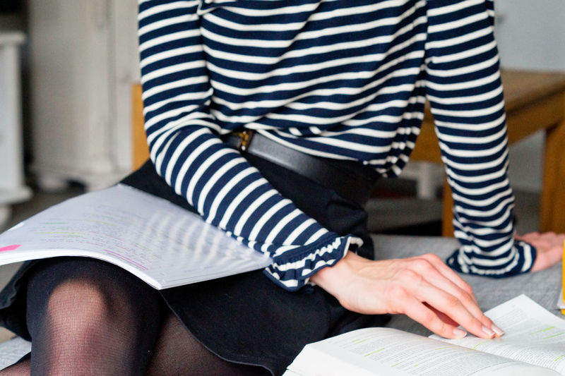 Midsection of woman with books sitting on sofa at home