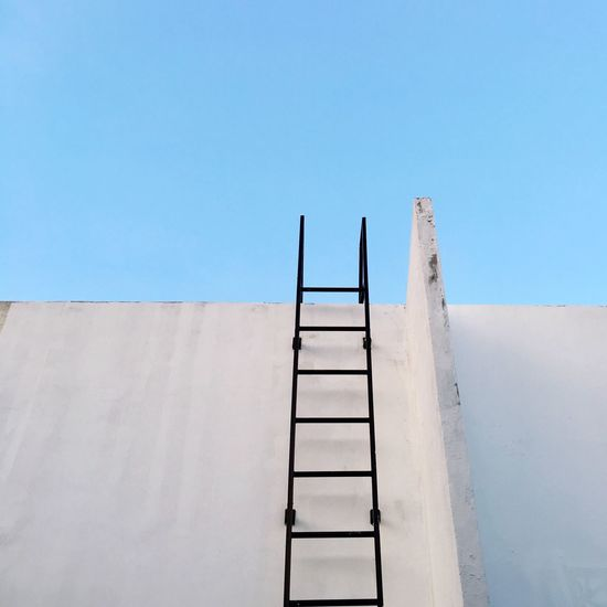 Low angle view of ladder on concrete wall against clear blue sky