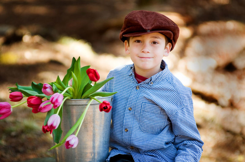 Young boy wearing a cap holding a bucket of tulip flowers outdoors. Beauty In Nature Boy Bucket Child Childhood Flower Flowers Happy Nature One Person Outdoors People Portrait Spring Springtime Tulips