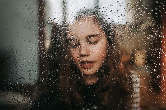 Close-up of girl seen through wet window in rainy season