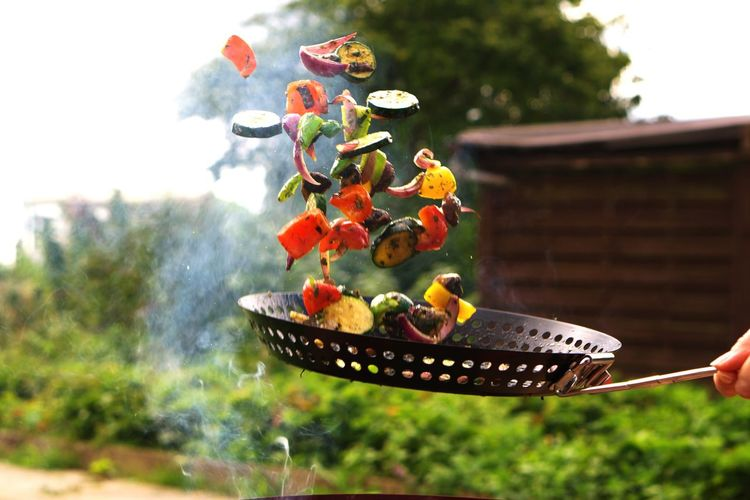 Cropped hand tossing vegetables while cooking outdoors