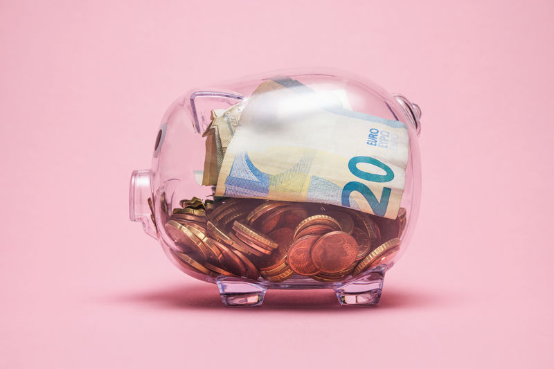 Close-up of currency in piggy bank over pink background
