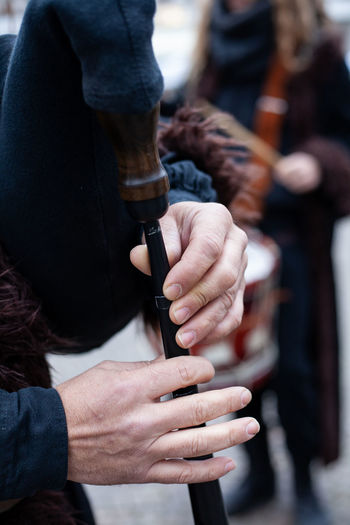 Close-Up Of Human Hands Playing Bagpipe In City