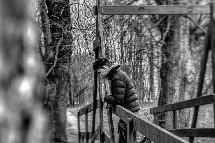 Side view of young man standing by railing in forest