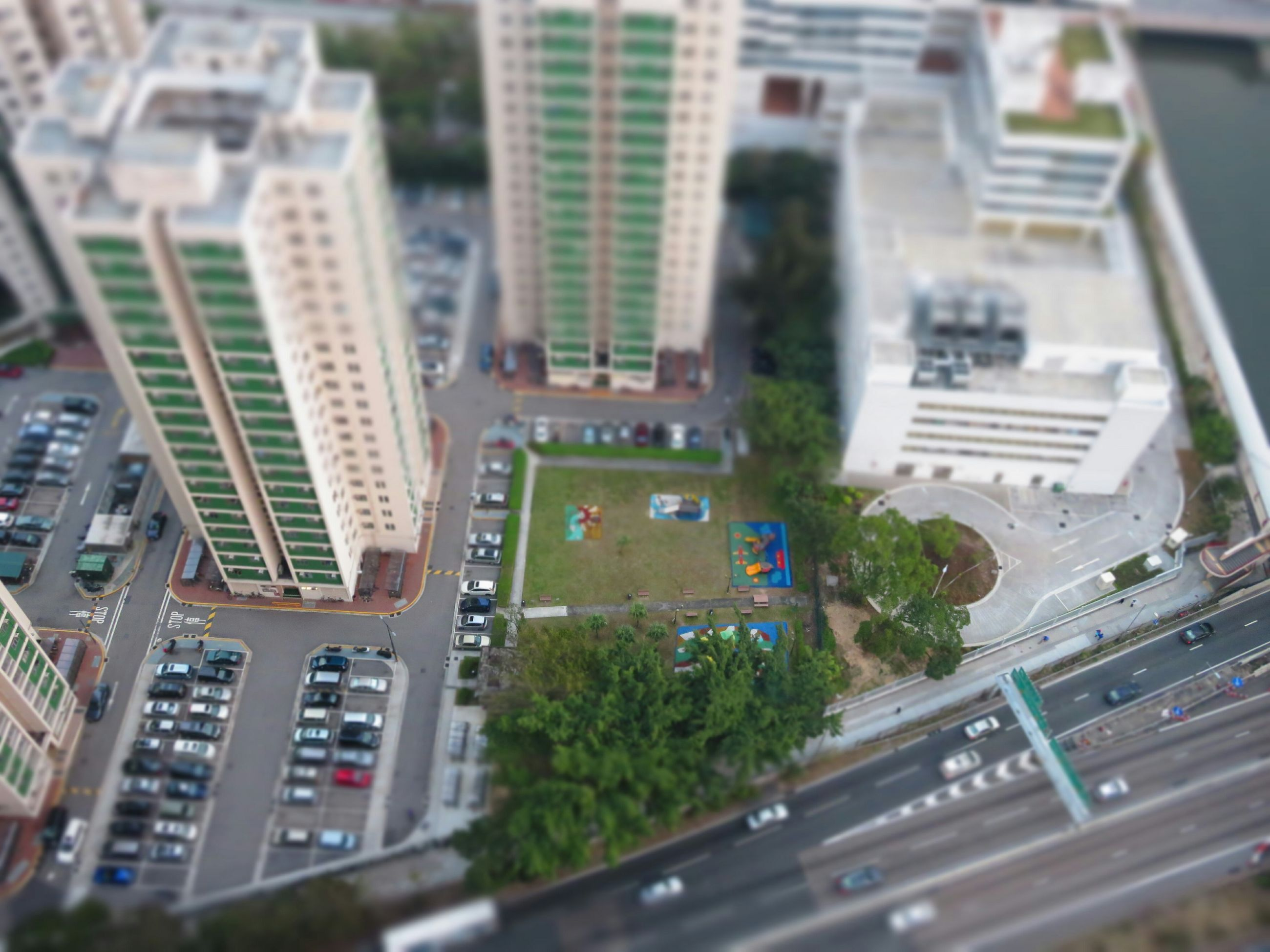 building exterior, architecture, city, built structure, transportation, car, high angle view, land vehicle, road, street, mode of transport, cityscape, skyscraper, city life, office building, traffic, city street, building, residential building, day