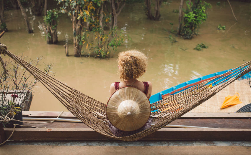 High Angle View Of Woman Sitting On Hammock By Swamp In Forest