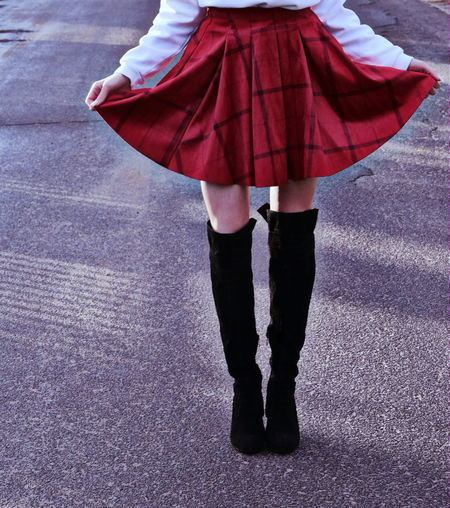 Low section of woman holding red skirt on road