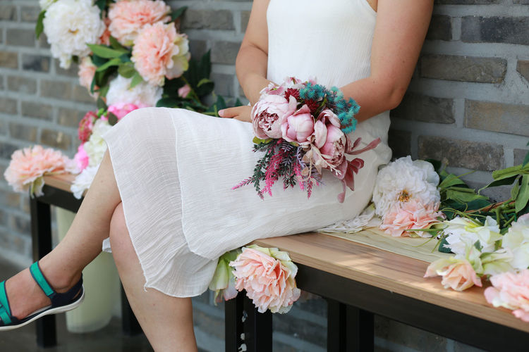 Midsection of bride holding flower bouquet while sitting on bench