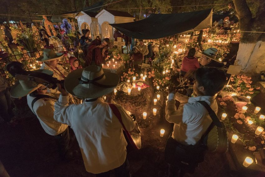 A musical group plays the deceased's favorite songs in front of his grave. The Night of the Dead in Mexico, and especially in Michoacan, is a celebration of joy for the return of the deceased, who return that night to live with their loved ones, according to tradition. Real People Group Of People Women Men Night Lifestyles Adult Illuminated People Crowd Leisure Activity Child High Angle View Rear View Childhood Females Togetherness Celebration